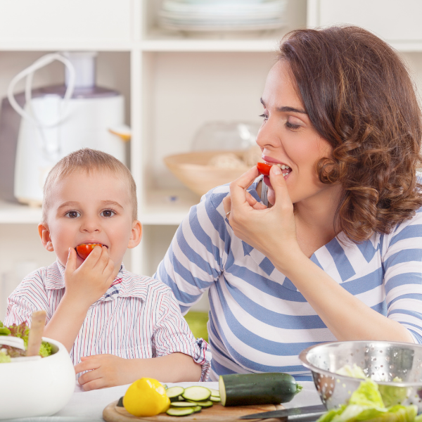 young son and mom eating vegetables