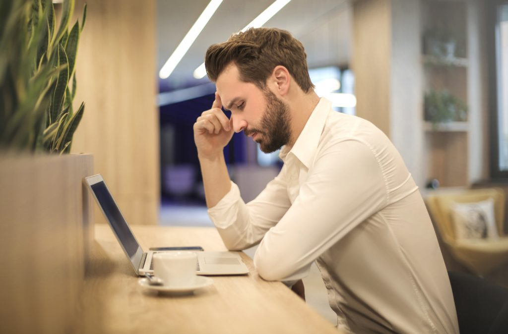 Adult Man with Computer Looking Stressed