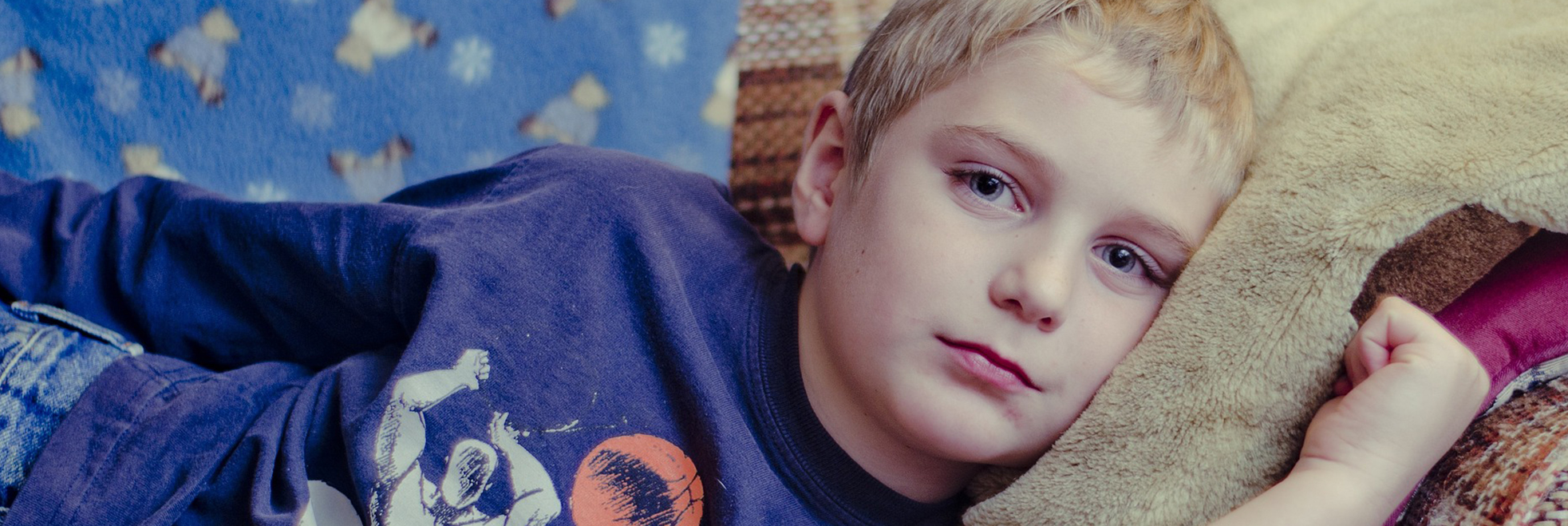 young blonde boy looking unhappy on couch