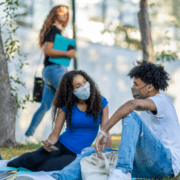 college students sitting on lawn with masks on