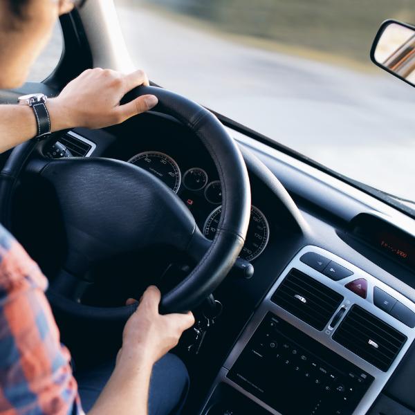 man driving hands on steering wheel