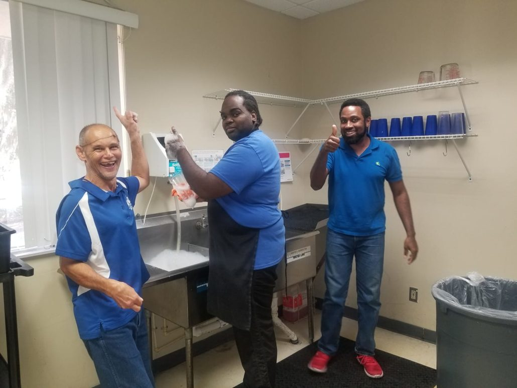 clubhouse members washing dishes and smiling at camera