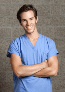 man in scrubs smiling with arms crossed