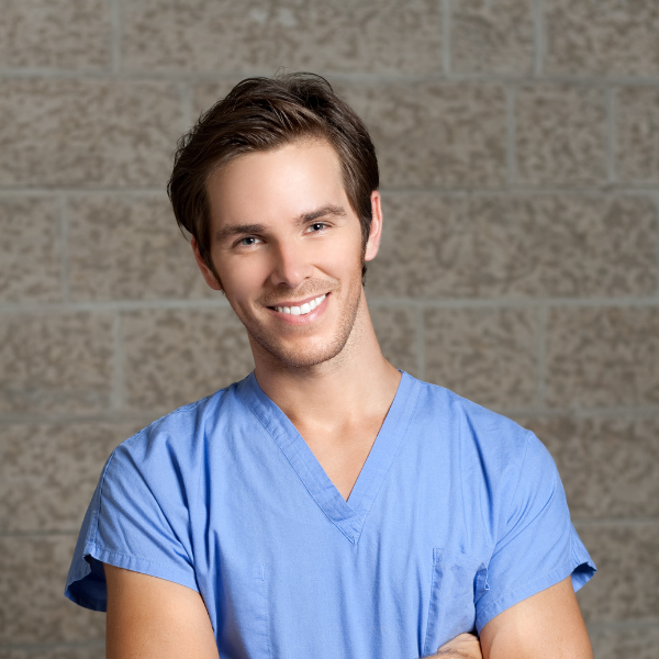 man in scrubs smiling with arms crossed featured image size